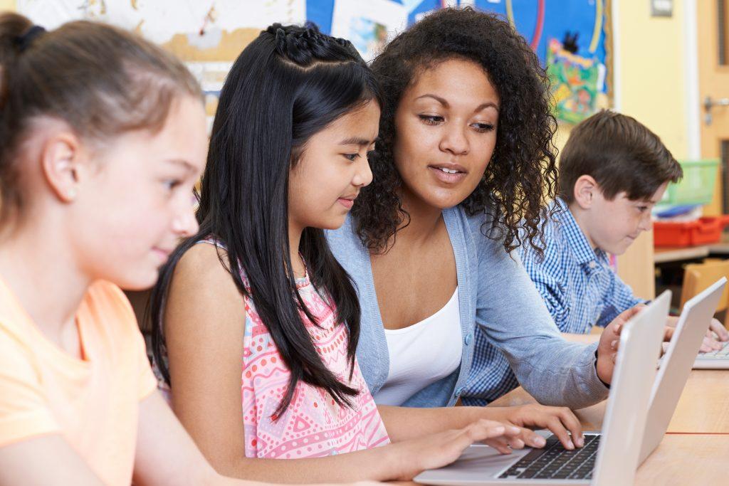 Teacher Appreciation: Teacher Helping Group Of Elementary School Children In Computer Class