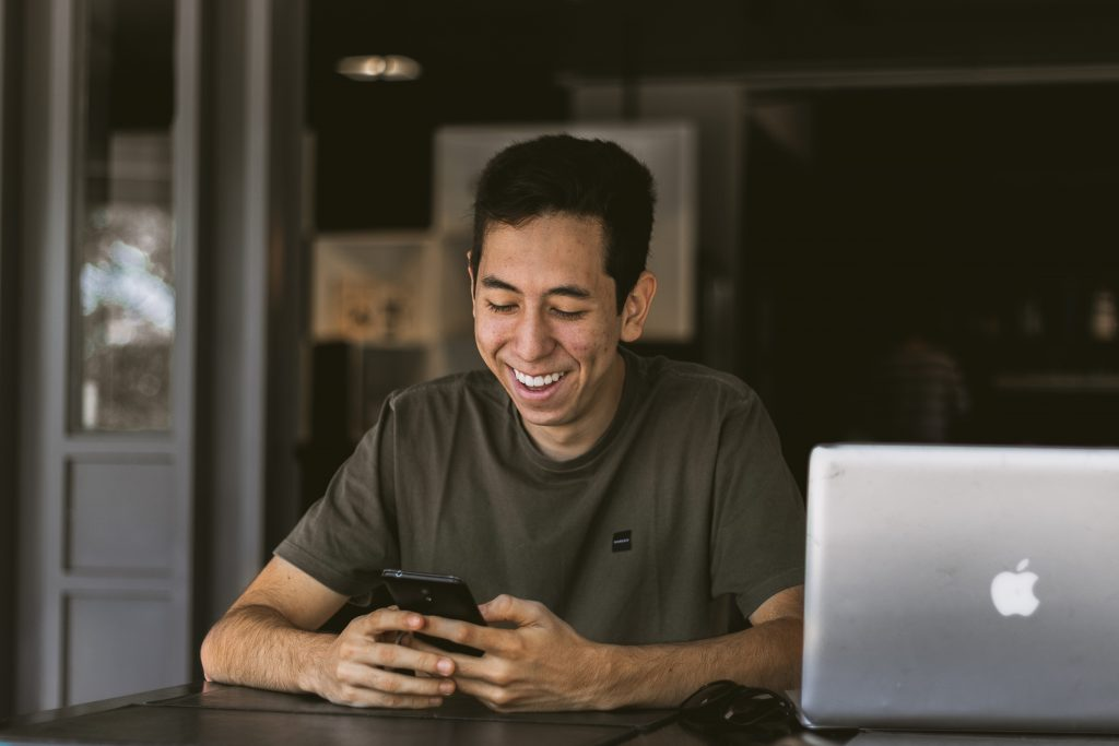Boy in Brown Shirt With Laptop Smiling at Phone
