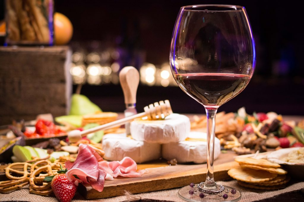 Wine Glass Filled with Red Wine Next to a Table with Assorted Meats and Cheeses