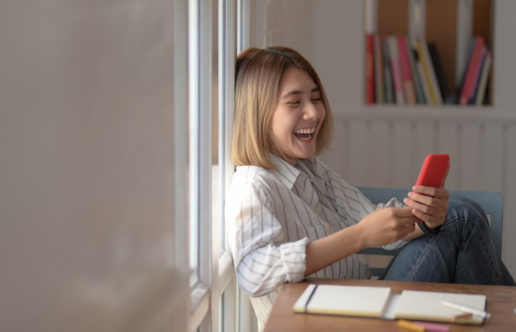 Joyous Woman Smiling at Her Smartphone