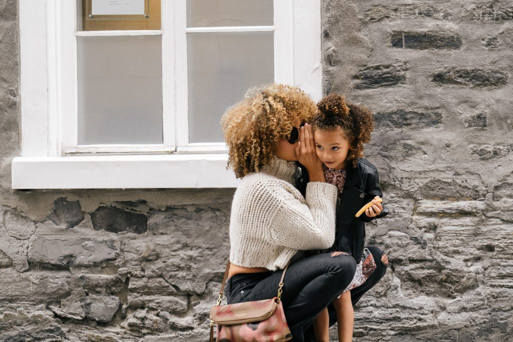 mom whispering into her daughters ear in front of a stone house
