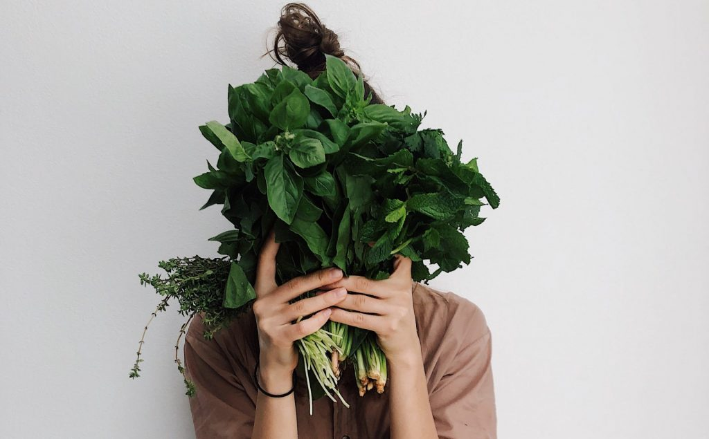 a woman holding a bouquet of herbs in front of her face