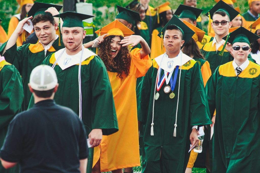 group of students in green cap and gown celebrating graduation